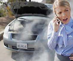 image - woman on cell phone, car in background overheating with smoke pouring out of engine.