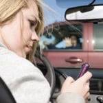 A teenager texting on her phone and looking away from the road where she is about to hit a truck with a woman in the drivers seat. - Transmission Repair - Car Repair - AAMCO Colorado