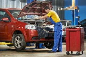 image - Mechanic working on car engine in repair shop.