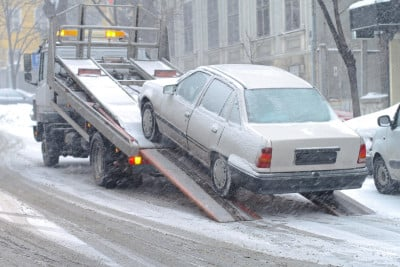 Image of car being ramped onto truck for towing in winter storm