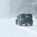 Jeep 4 wheel driving on snowy mountain road in snowstorm