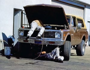 image of two guys working on four-wheel-drive SUV engine, one under hood, one under car.
