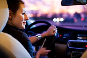image of woman steering her car, driving at night.