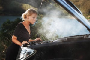 image of woman looking into smoking engine, hood up.