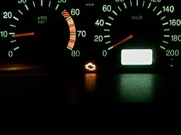 image of dashboard speedometer, tachometer with illuminated check engine light.