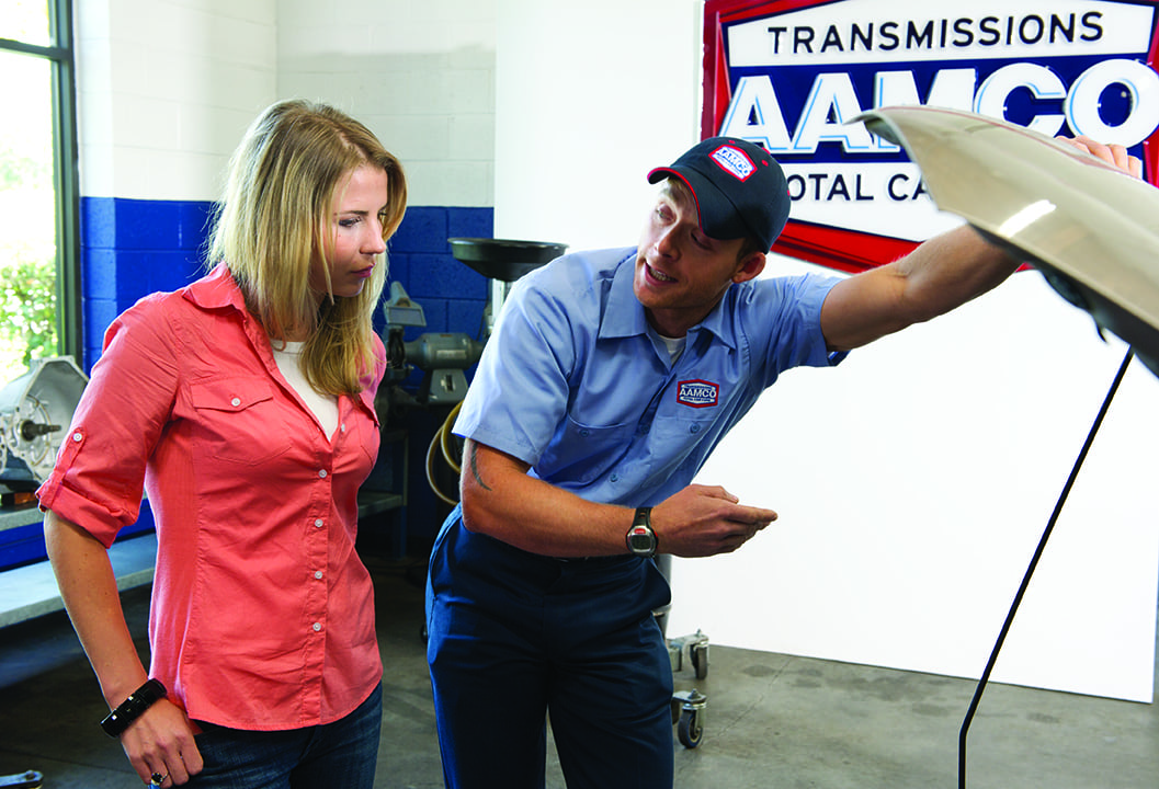 image of AAMCO mechanic showing customer engine and talking about recommended maintenance.