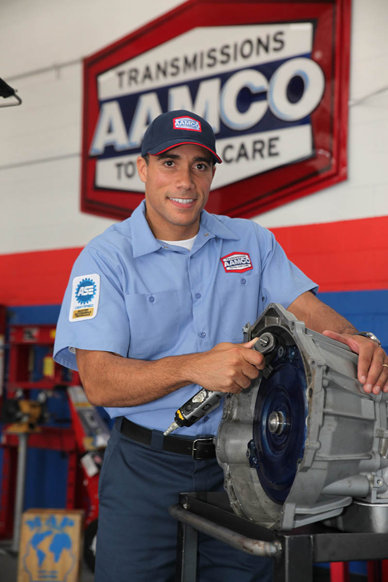 image of smiling AAMCO tranmission technician with a transmission main planetary gear housing