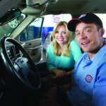 image of happy customer and AAMCO mechanic sitting in car with customer.