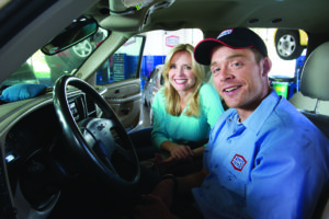 image of happy customer and AAMCO mechanic sitting in customer's car.