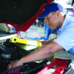 image of AAMCO Colorado mechanic working on engine, under hood.