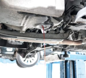 image of car on lift, transmission fluid draining out of transmission.
