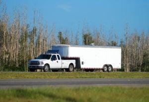 image - pickup truck towing towing large trailer.