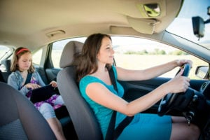 image of mother driving car and child sitting on back seat and playing with tablet.