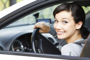 image of girl smiling, sitting in driver seat, hand on steering wheel, looking at you over shoulder out window.