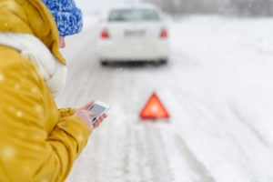 image of woman stranded in freezing winter weather at side of road, car broken down, while she dials for help on cell phone.