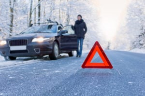 image of car breakdown on winter freezing forest road, stranded side of road, warning triangle in road.