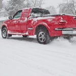 image of red pickup truck 4x4 spinning wheels snowy icy street