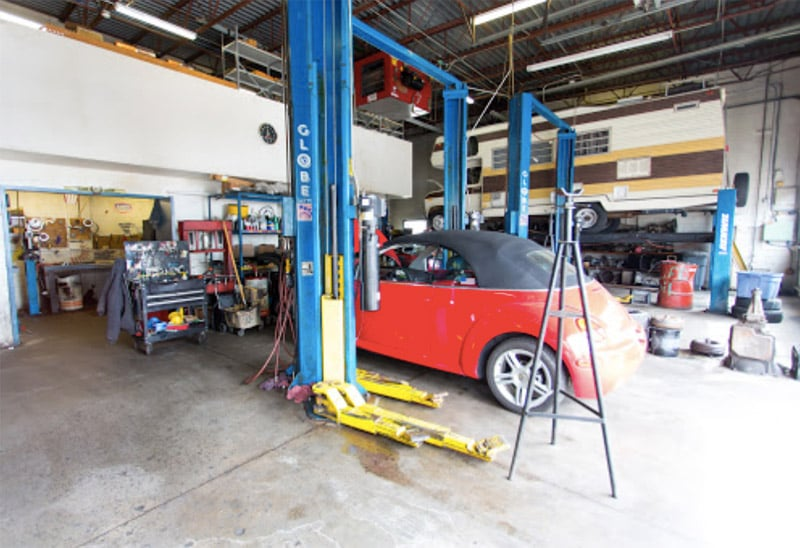image of AAMCO Littleton interior repair bay with car ready to go on lift