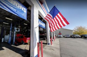 image of AAMCO Greeley exterior service bay, American flag waving in breeze.