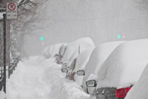 Cars stuck under heavy snow on the side of the road