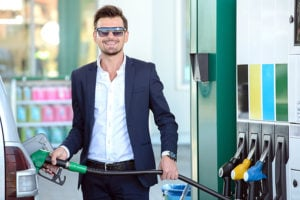 Young businessman in a suit refueling car tank at fuel station