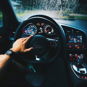 Image of man using cruise control with hand on steering wheel