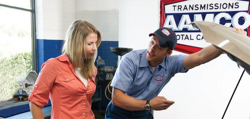 aamco mechanic holding open hood for aamco customer